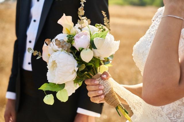Detail svatební kytice, kterou drží v ruce nevěsta, v pozadí postava ženicha