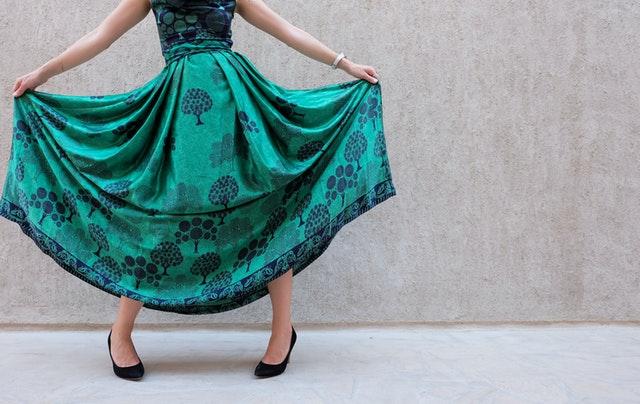 Žena držící v rukou roztaženou sukni společenských šatů