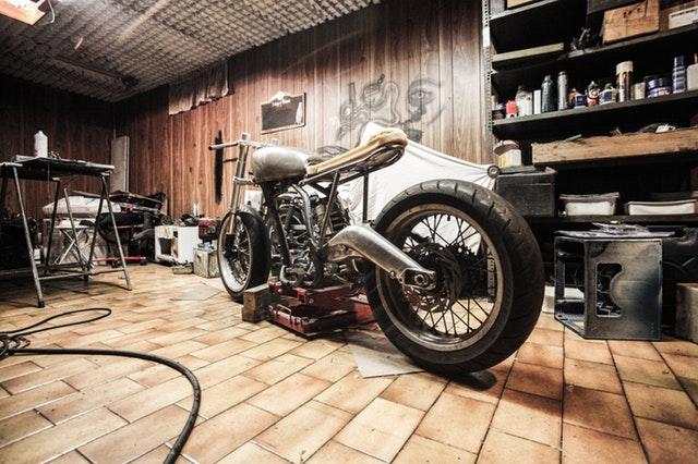 motorka v garáži, kolem je mnoho dalších věcí, starší kousek, který se opravuje